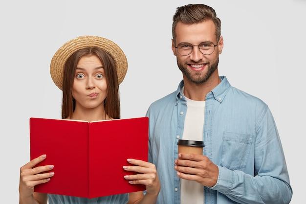 Surpris beau couple posant contre le mur blanc