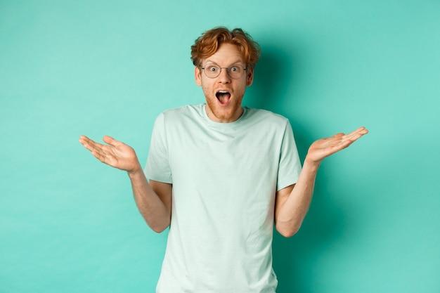 Surpris bel homme aux cheveux roux, portant des lunettes, écartant les mains sur le côté et haletant d'émerveillement, regardant étonné à la caméra, debout sur fond turquoise.