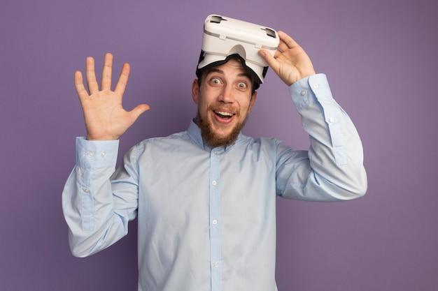 Surpris bel homme blond détient casque vr et se dresse avec la main levée isolé sur mur violet