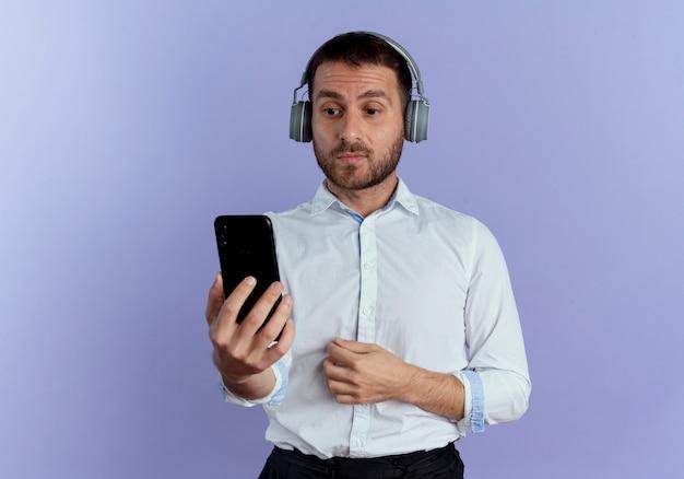 Surpris bel homme sur le casque tient et regarde le téléphone isolé sur le mur violet