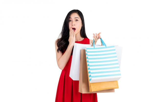 Surpris belle cliente asiatique portant de nombreux sacs à provisions
