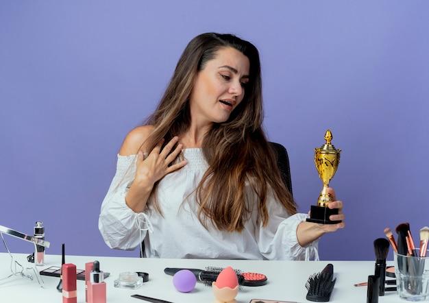 Surpris belle fille est assise à table avec des outils de maquillage met la main sur la poitrine et se penche sur la coupe du gagnant isolé sur le mur violet