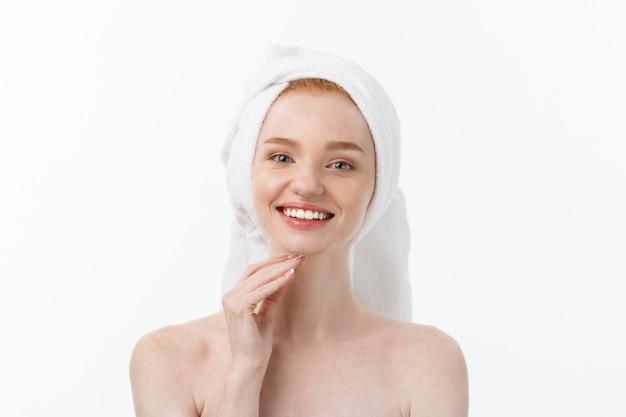 Surpris de belle jeune femme après le bain avec une serviette sur la tête isolée sur fond blanc.
