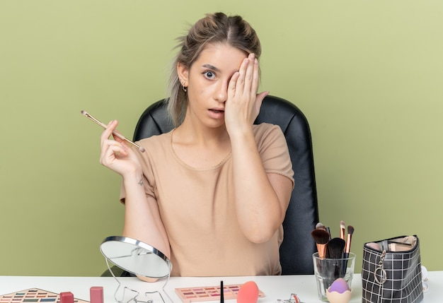 Surpris belle jeune fille assise au bureau avec des outils de maquillage tenant un pinceau de maquillage oeil couvert avec la main isolée sur fond vert olive
