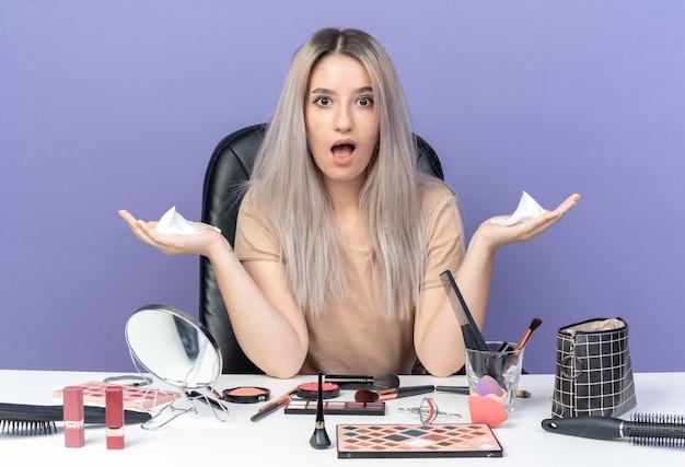 Surpris, belle jeune fille est assise à table avec des outils de maquillage tenant de la crème pour les cheveux écartant les mains isolées sur fond bleu