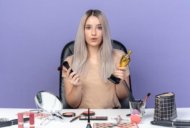 Surpris, belle jeune fille est assise à table avec des outils de maquillage tenant une tasse gagnante avec un pinceau de maquillage isolé sur fond bleu