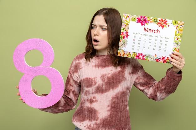 Surpris belle jeune fille le jour de la femme heureuse tenant le numéro huit avec calendrier