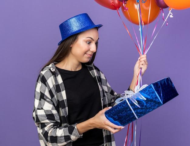 Surpris belle jeune fille portant un chapeau de fête tenant des ballons et regardant une boîte-cadeau dans sa main