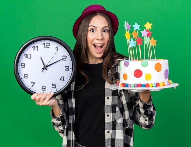 Surpris belle jeune fille portant un chapeau de fête tenant un gâteau avec une horloge murale