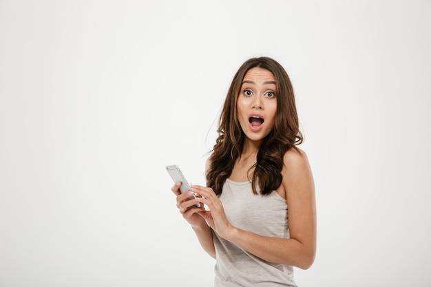 Surpris brunette woman holding smartphone et regardant la caméra avec la bouche ouverte sur gris