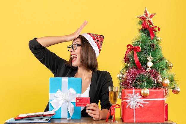 Surpris charmante dame en costume avec chapeau de père noël et lunettes pointant cadeau et carte bancaire au bureau sur jaune isolé