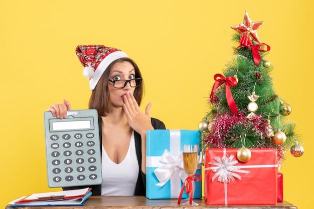 Surpris charmante dame en costume avec chapeau de père noël montrant la calculatrice dans le bureau sur jaune isolé