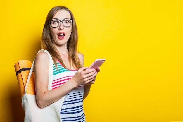 Surpris choqué jeune femme karimat dans un sac tenant un téléphone sur fond jaune.