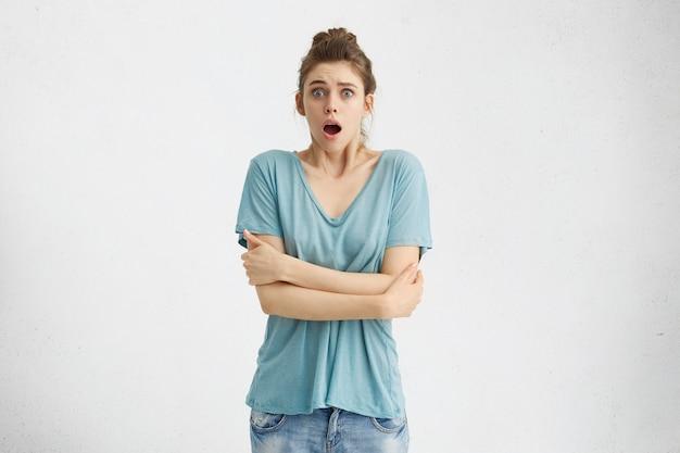 Surpris et choqué, jeune femme de race blanche vêtue de vêtements décontractés regardant la bouche ouverte et les yeux sortis, gardant les bras croisés
