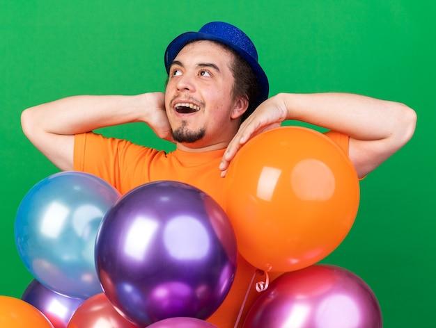 Surpris à côté jeune homme portant un chapeau de fête debout derrière des ballons mettant la main sur la joue