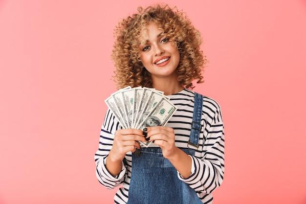 Surpris, curly, femme, 20s, tenue, fan, de, dollar, argent, quoique, debout