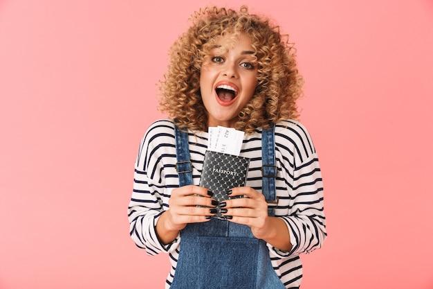 Surpris curly woman 20s tenant un passeport et des billets de voyage en position debout