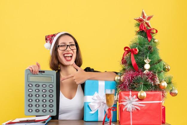 Surpris drôle de charmante dame en costume avec chapeau de père noël montrant la calculatrice au bureau sur jaune isolé
