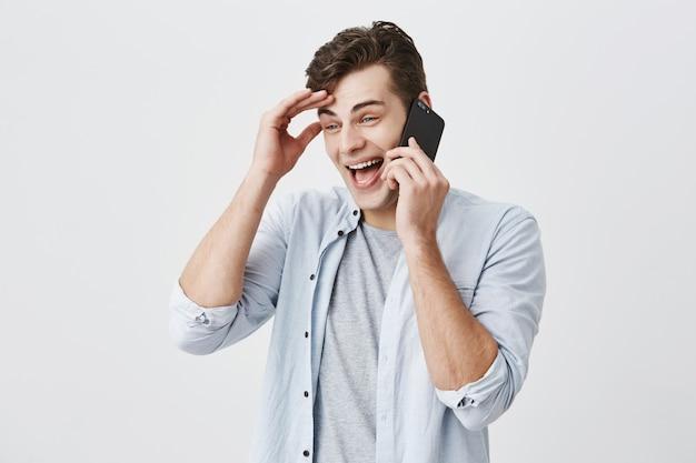 Surpris émotionnel jeune homme caucasien avec maison sombre, portant une chemise bleu clair souriant tout en ayant une conversation agréable avec sa petite amie, toucher le front, largement souriant, partager de bonnes nouvelles.