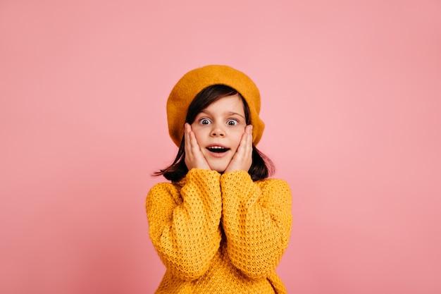 Surpris enfant bien habillé touchant le visage. fille préadolescente émotionnelle isolée sur mur rose.