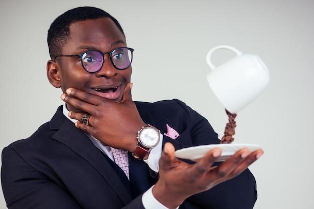 Surpris et étonné, bel homme d'affaires afro-américain dans un costume classique noir et des lunettes tenant une tasse avec des éclaboussures de grains de café volants sur une assiette sur fond blanc tourné en studio. boisson magique du matin