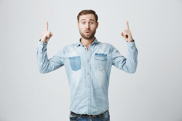 Surpris et étonné bel homme pointant les doigts vers le haut
