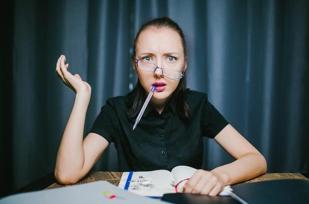 Surpris l'étudiant assis à une table avec un stylo dans la bouche