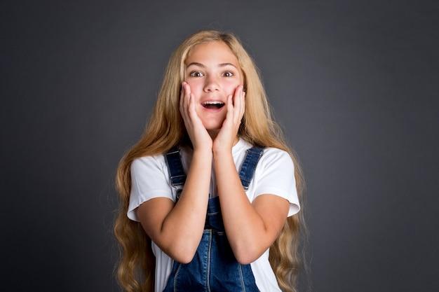 Surpris ou excité belle adolescente sur fond gris.