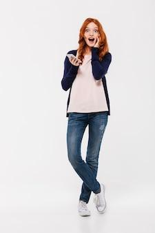 Surpris excité belle jeune femme rousse bavardant par téléphone mobile.