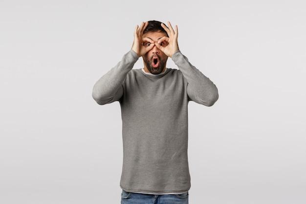 Surpris, excité et fasciné bel homme barbu en pull gris, faites le tour des doigts sur les yeux comme des lunettes ou des jumelles, bouche ouverte haletant amusé, voyez et consultez la promo génial
