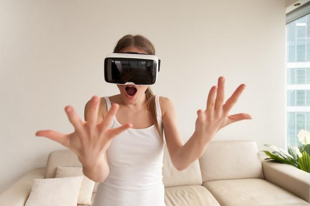 Surpris excité jeune fille portant des lunettes de réalité virtuelle regardant à la main