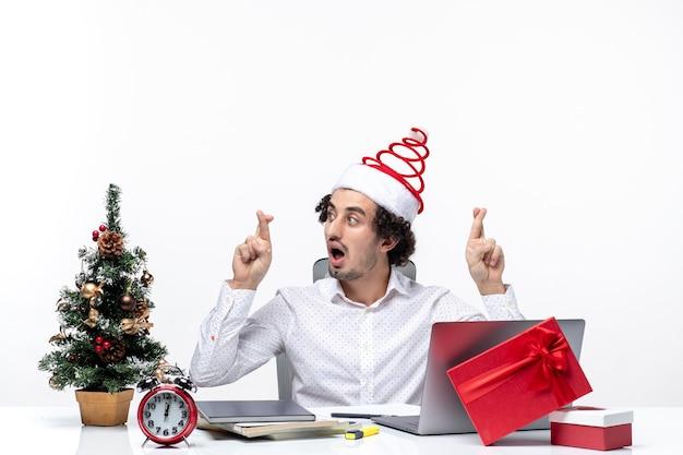 Surpris excité jeune homme d'affaires avec drôle de chapeau de père noël croisant les doigts pour la chance au bureau sur fond blanc