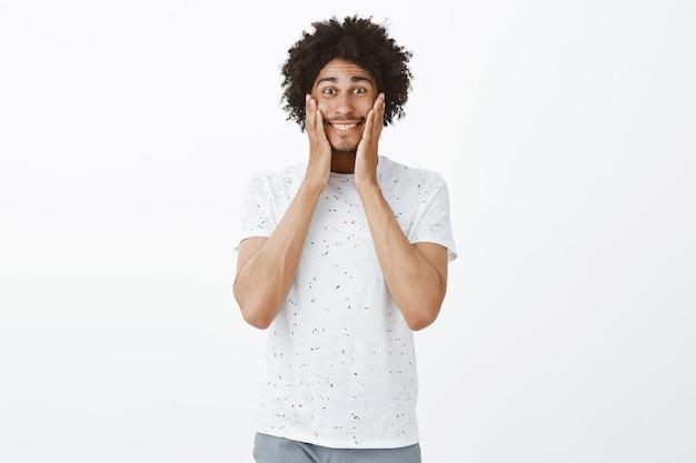 Surpris et excité, joyeux homme à la peau sombre se réjouissant de la bonne nouvelle