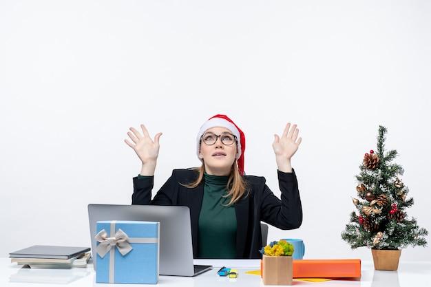 Surpris femme d'affaires avec chapeau de père noël assis à une table avec un arbre de noël et un cadeau dessus pointant au-dessus sur fond blanc