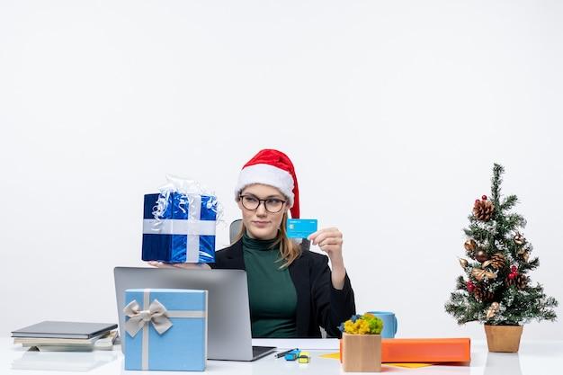 Surpris femme d'affaires avec chapeau de père noël et portant des lunettes assis à une table tenant un cadeau de noël et une carte bancaire sur fond blanc