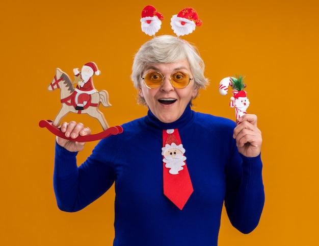 Surpris femme âgée dans des lunettes de soleil avec bandeau de père noël et cravate de père noël tenant le père noël sur la décoration de cheval à bascule et canne en bonbon isolé sur fond orange avec espace de copie