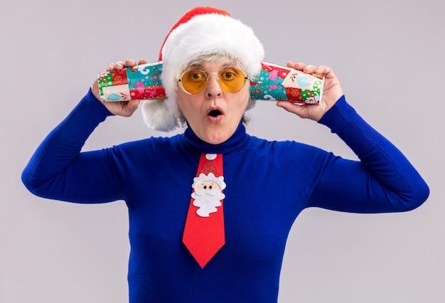 Surpris femme âgée dans des lunettes de soleil avec bonnet de noel et cravate de père noël tenant des gobelets en papier près des oreilles isolé sur fond blanc avec espace copie