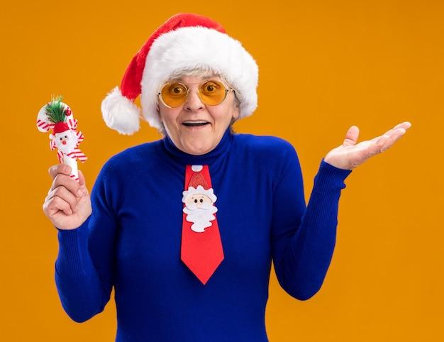 Surpris femme âgée dans des lunettes de soleil avec bonnet de noel et cravate de père noël tient la canne en bonbon et garde la main ouverte isolée sur fond orange avec espace de copie