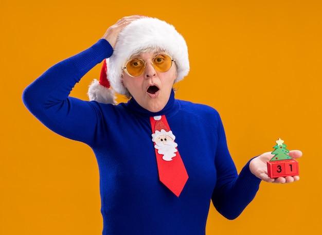 Surpris femme âgée dans des lunettes de soleil avec bonnet de noel et cravate de père noël tient l'ornement d'arbre de noël et met la main sur la tête isolée sur fond orange avec espace copie