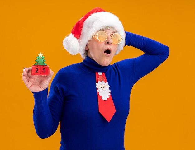 Surpris femme âgée dans des lunettes de soleil avec bonnet de noel et cravate de père noël tient l'ornement d'arbre de noël et met la main sur la tête en regardant côté isolé sur fond orange avec espace de copie