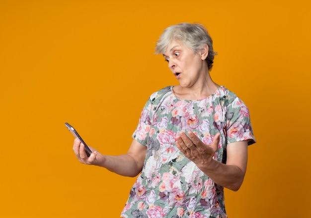 Surpris femme âgée lève la main et regarde le téléphone isolé sur le mur orange