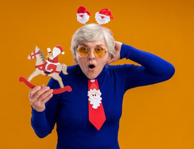 Surpris femme âgée à lunettes de soleil avec bandeau de père noël et cravate de père noël tient le père noël sur la décoration de cheval à bascule isolé sur fond orange avec espace de copie