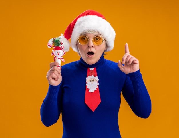 Surpris femme âgée à lunettes de soleil avec bonnet de noel et cravate de père noël détient la canne en bonbon et pointe vers le haut isolé sur fond orange avec espace copie