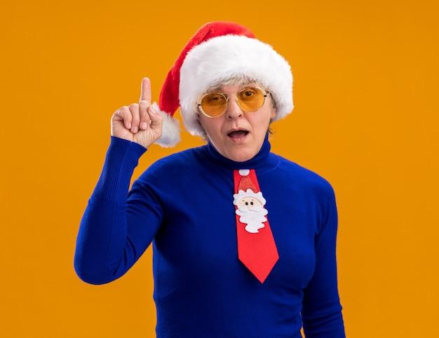 Surpris femme âgée à lunettes de soleil avec bonnet de noel et cravate de père noël pointant vers le haut isolé sur fond orange avec espace de copie