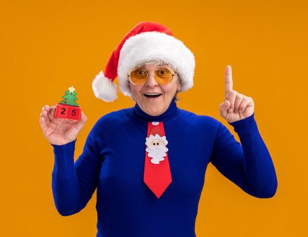Surpris femme âgée à lunettes de soleil avec bonnet de noel et cravate de père noël tenant ornement d'arbre de noël et pointant vers le haut isolé sur fond orange avec espace copie