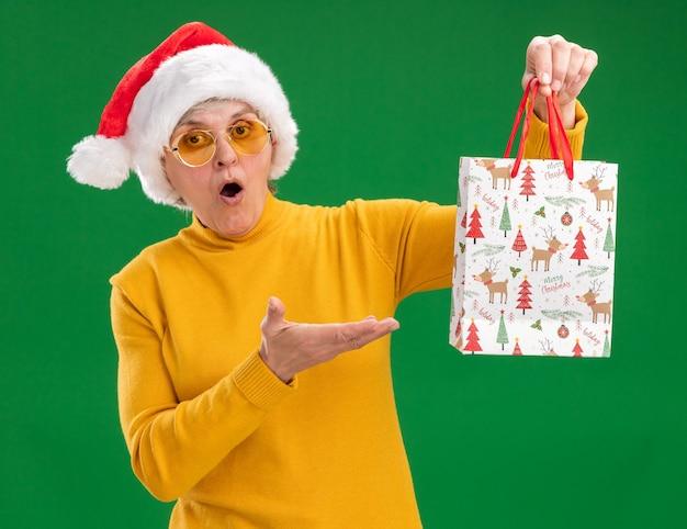 Surpris femme âgée à lunettes de soleil avec bonnet de noel tenant et pointant sur sac-cadeau en papier isolé sur fond vert avec espace copie