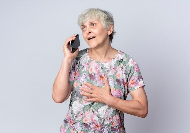 Surpris femme âgée met la main sur le menton tient le téléphone à côté isolé sur mur blanc