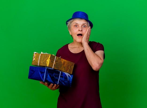 Surpris femme âgée portant chapeau de fête met la main sur le visage tenant des coffrets cadeaux sur vert