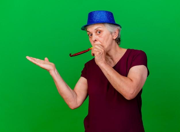 Surpris femme âgée portant chapeau de fête soufflant sifflet et gardant la main ouverte sur le vert