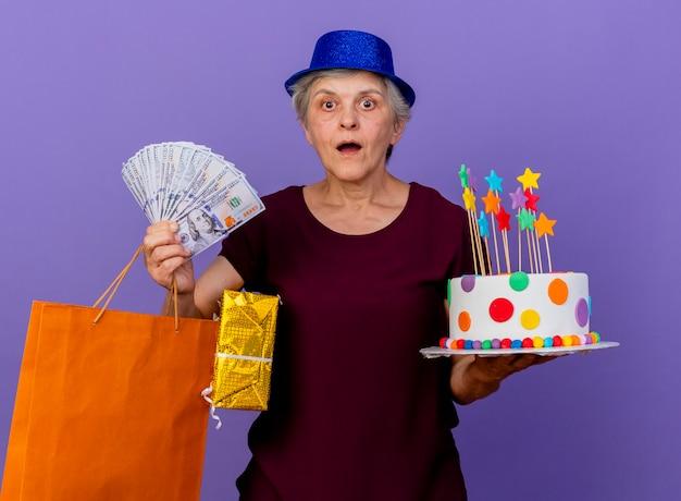 Surpris femme âgée portant chapeau de fête tient un gâteau d'anniversaire boîte-cadeau d'argent